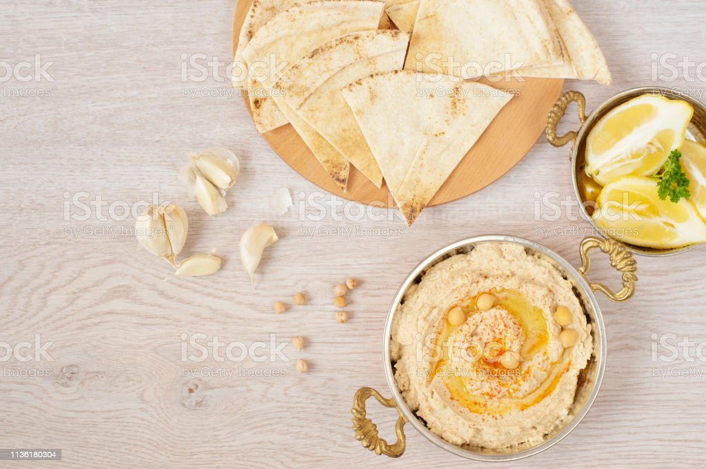 Homemade hummus with olive oil on a light background. Arabic bread on a wooden board stock photo