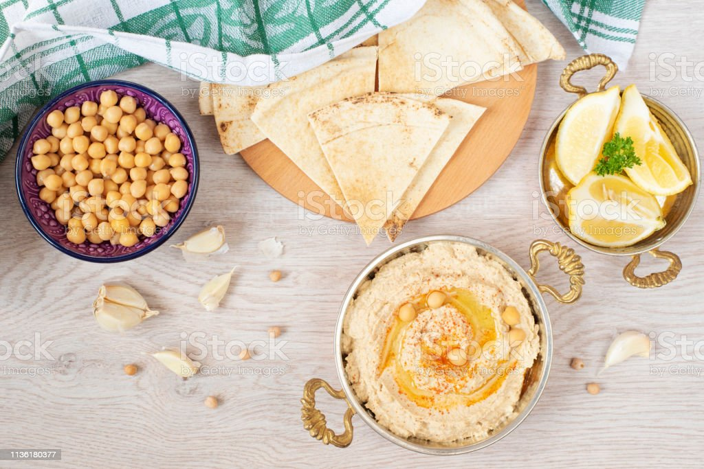 Homemade hummus with olive oil on a light background. Arabic bread, chickpeas and lemon around stock photo