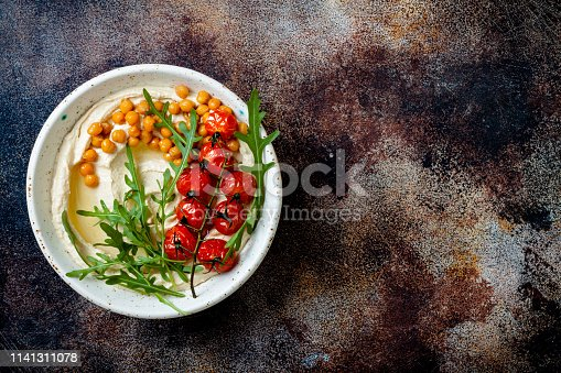 istock Homemade hummus with roasted cherry tomatoes and pita bread. Middle Eastern traditional and authentic arab cuisine. Top view, flat lay, overhead 1141311078