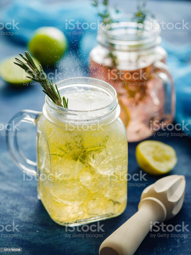 Homemade Iced fizzy Sparkling lemonade with lemon, rosemary and thyme in Mason jar. стоковое фото