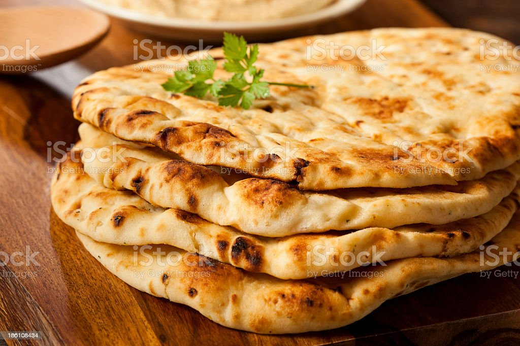 Homemade Indian Naan flatbread stacked on a cutting board stock photo