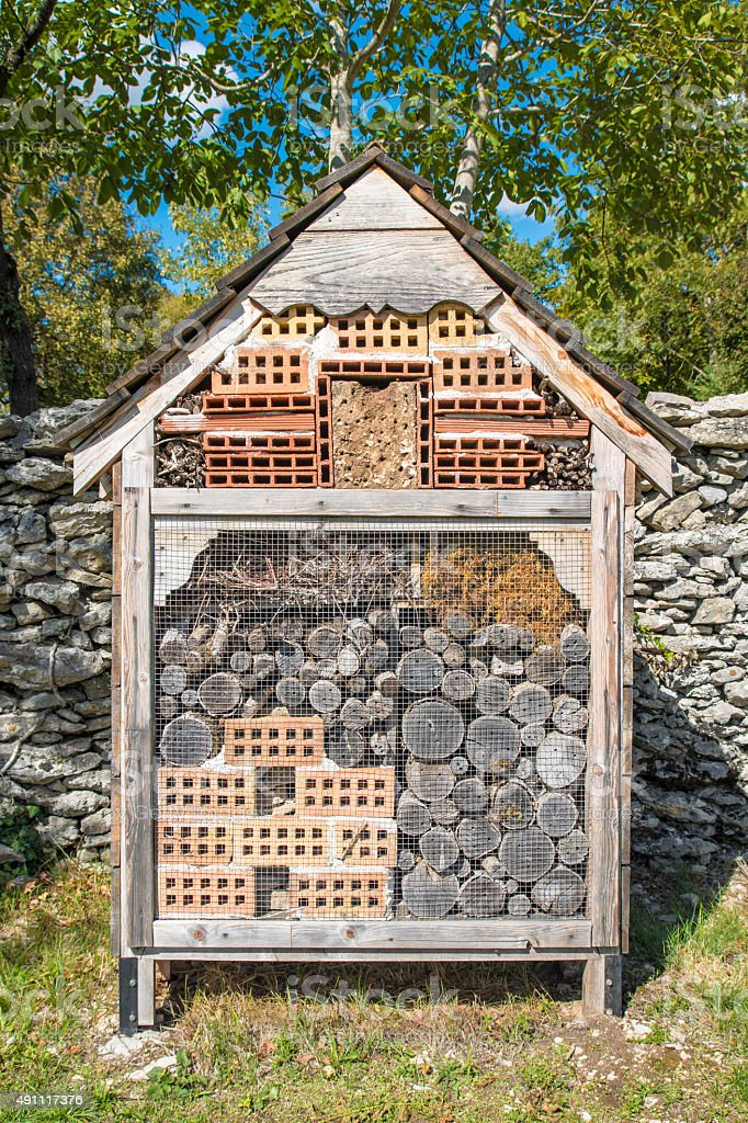 homemade insects hotel house in garden with bricks and logs royalty free stock photo