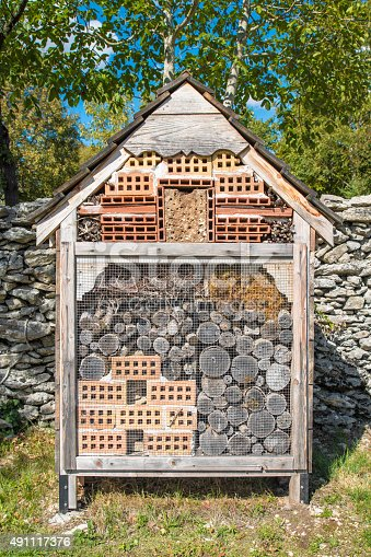 Vertical composition photography of insects hotel wooden house outdoor, homemade in garden during a sunny day, shot without people. Made with bricks and logs from tree to host an insect animal biodiversity.