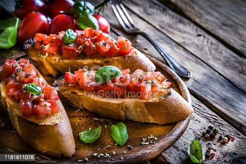 Italian food: homemade bruschetta ready to eat shot on rustic wooden table. Olive oil, tomatoes and peppercorns complete the composition. Predominant colors are red and brown. XXXL 42Mp studio photo taken with Sony A7rii and Sony FE 90mm f2.8 macro G OSS lens