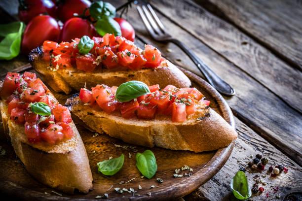 bruschetta italiano caseiro na tabela de madeira rústica - comida italiana - fotografias e filmes do acervo
