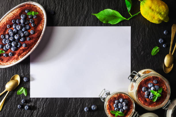 hausgemachte italienische dessert tiramisu in einzelne gläser mit minze und kakaopulver, heidelbeere, zitrone über schwarzen konkreten hintergrund, textfreiraum serviert. essen-hintergrund. briefe von mehl - weihnachtlich tiramisu stock-fotos und bilder