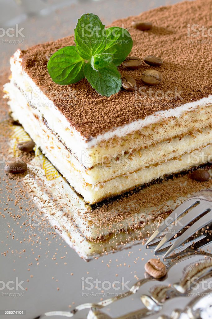 Homemade Italian dessert tiramisu with mint and coffee beans on stock photo