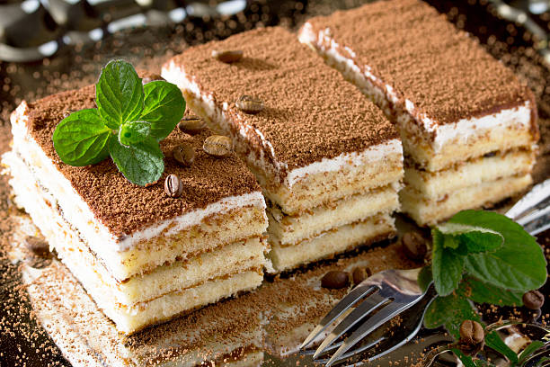 Homemade Italian dessert tiramisu with mint and coffee beans on Homemade Italian dessert tiramisu with mint and coffee beans on a metal plate. tiramisu stock pictures, royalty-free photos & images