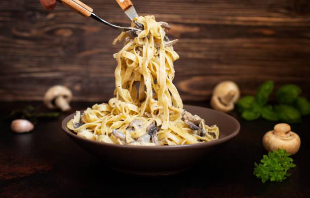 homemade italian fettuccine pasta with mushrooms and cream sauce (fettuccine al funghi porcini). traditional italian cuisine. served on a dark table with a rustic wooden background. close-up - cogumelos imagens e fotografias de stock