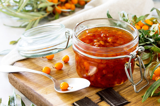 istock Homemade jam. Glass jar with sea buckthorn jam on rustic background. Preserved berry. Copy space. 1048165286