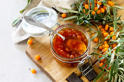 istock Homemade jam. Glass jar with sea buckthorn jam on rustic background. Preserved berry. 1048165322