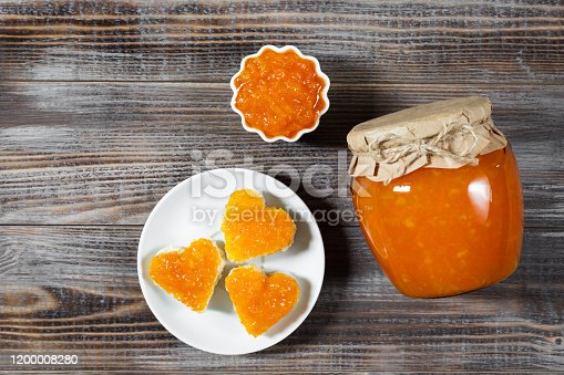 Homemade jam in a glass jar and bowl on a dark brown wooden background. Copy space. Top view, flat lay.