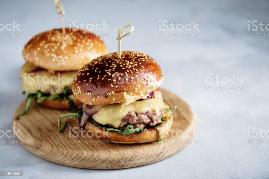 Homemade juicy burger with beef, cheese and caramelized onions. Street food, fast food. Copyspace. стоковое фото