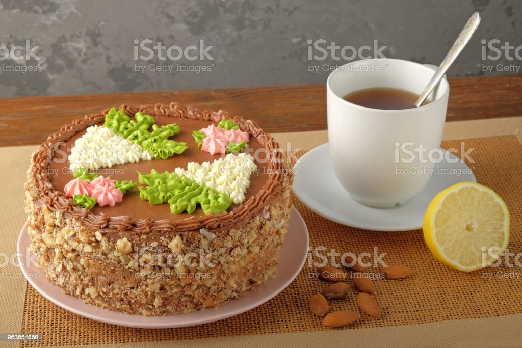 Homemade Kiev cake, cup of tea and scattered almonds on textile napkin - Royalty-free Baked Stock Photo