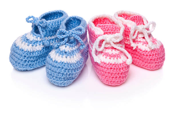Homemade knitted baby blue and pink booties stock photo