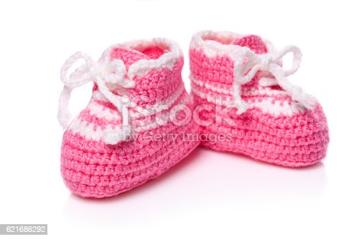 Homemade knitted baby pink booties isolated on white background