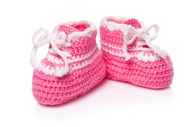 Homemade knitted baby pink booties stock photo