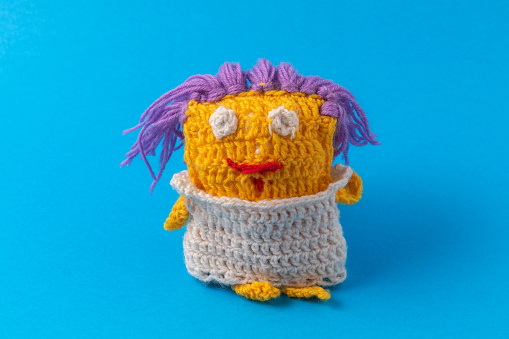 Funny knitted cartoon multi-colored toy for a child. Homemade creativity and hobbies