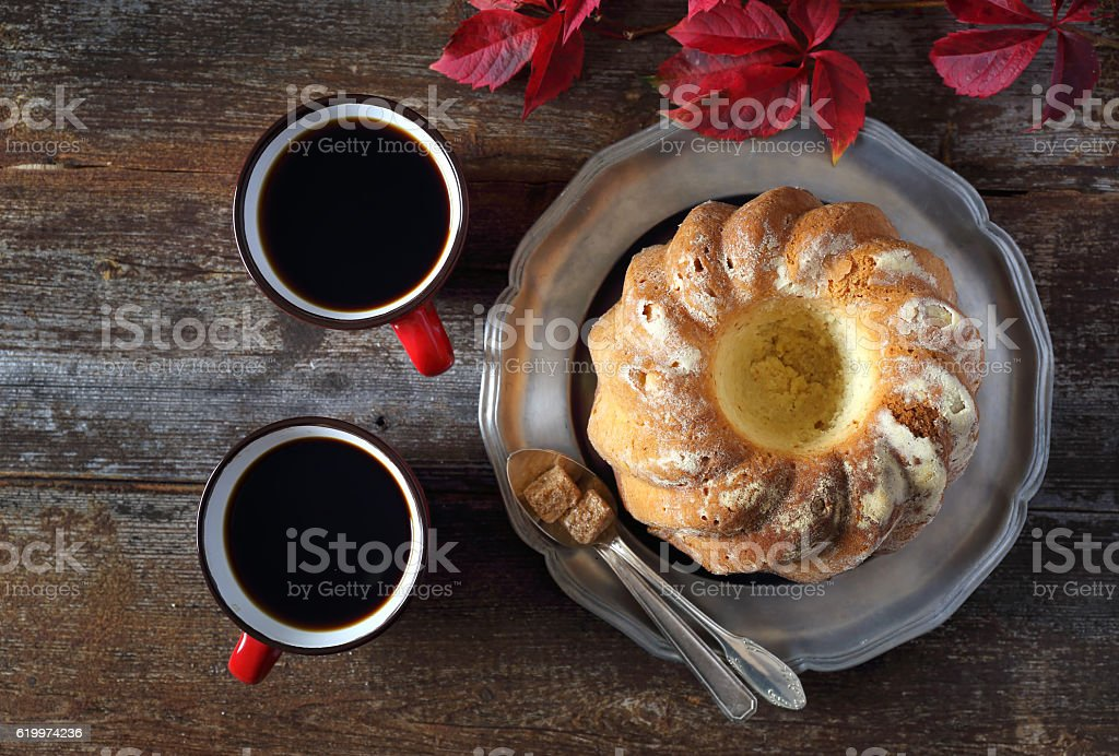 Homemade Kouglof, two cups of coffee and autumn leaves stock photo