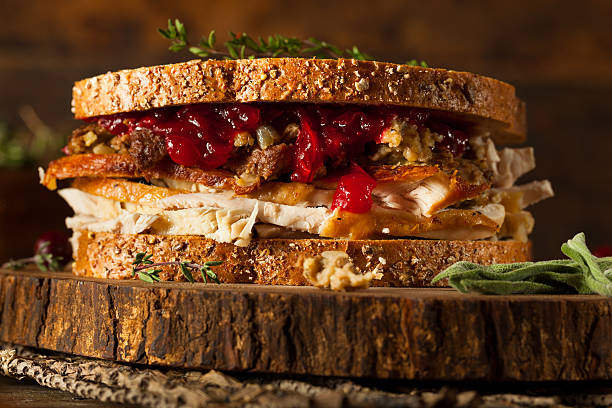 Homemade Leftover Thanksgiving Sandwich Homemade Leftover Thanksgiving Sandwich with Turkey Cranberries and Stuffing leftovers stock pictures, royalty-free photos & images