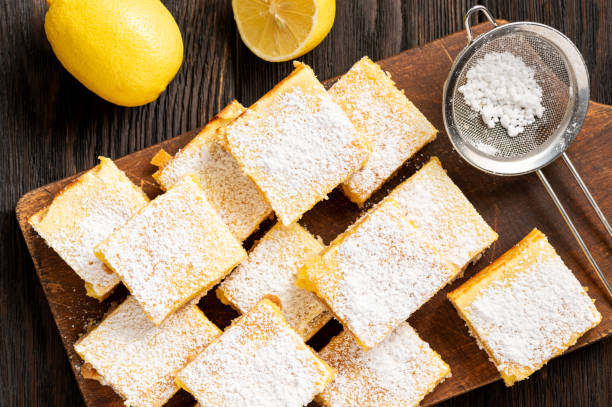 Homemade lemon bars with shortbread crust, on wooden background. stock photo