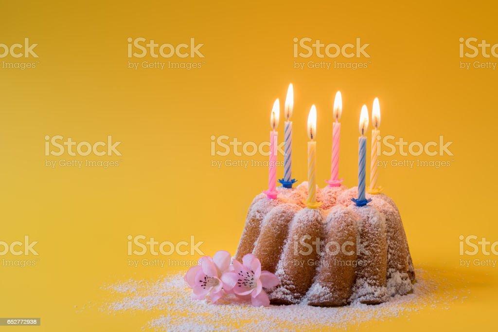 Homemade lemon bundt cake with icing sugar and burning candles - Photo