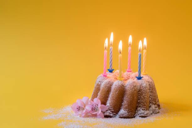 Bolo caseiro do bundt do limão com açúcar de crosta de gelo e velas ardentes - foto de acervo