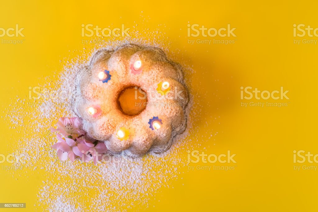 Homemade lemon bundt cake with icing sugar and burning candles - Top view foto
