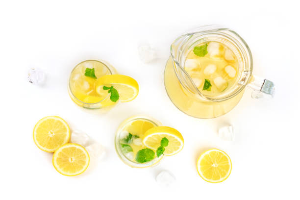 Homemade lemonade in glasses and a jar, with fresh lemons, mint, and ice cubes, shot from the top on a white background with copy space Homemade lemonade in glasses and a jar, with fresh lemons, mint, and ice cubes, shot from the top on a white background with copy space lemon juice stock pictures, royalty-free photos & images