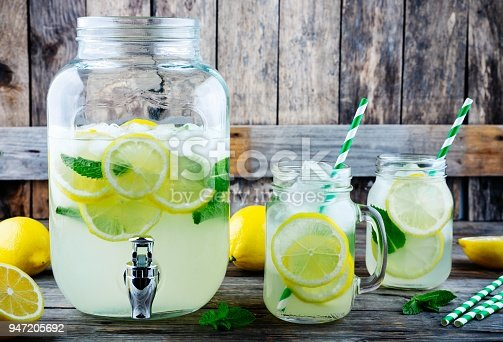 Homemade lemonade with mint, ice, and fresh lemon slices in mason jar on wooden background