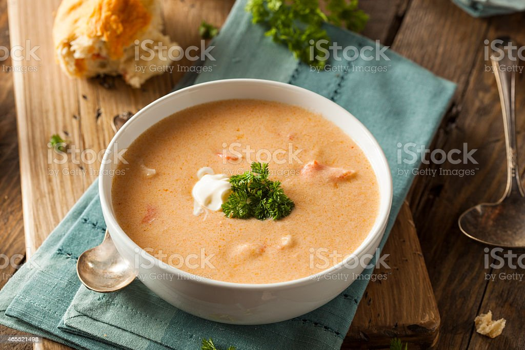 Homemade lobster bisque soup with a roll and garnish stock photo