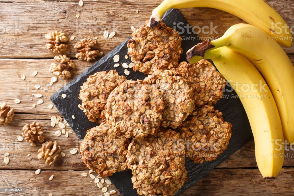 Homemade low-calorie banana cookies with oatmeal and walnuts close-up on a slate board. Horizontal top view Homemade low-calorie banana cookies with oatmeal and walnuts close-up on a slate board on the table. Horizontal top view from above Above Stock Photo