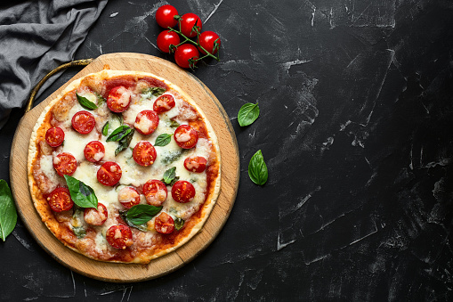 Homemade margarita pizza on a black stone background. Traditional italian food. Rustic style. Top view, flat lay, copy space