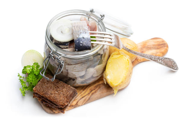homemade marinated herring in glass jar with rye bread and jacket potato isolated on white - herring stock photos and pictures
