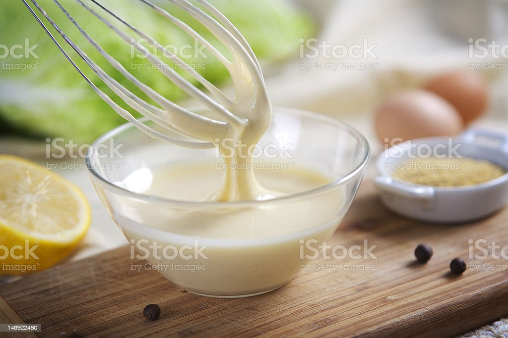 Homemade mayonnaise being whipped in a glass bowl stock photo