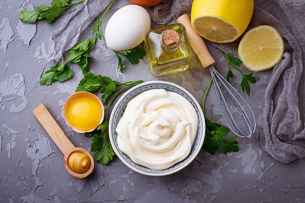 Homemade mayonnaise sauce and olive oil, eggs, mustard, lemon stock photo