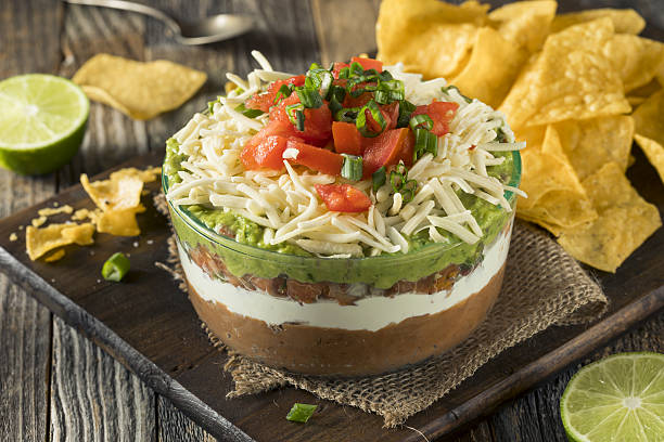 Homemade Mexican 7 Layer Dip Homemade Mexican 7 Layer Dip with Beans, Sour Cream and Guacamole dipping sauce stock pictures, royalty-free photos & images