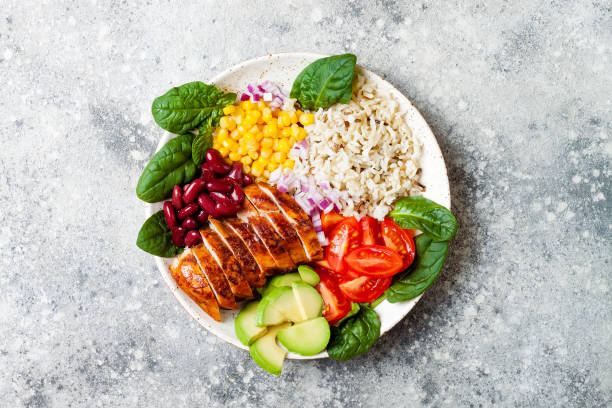 homemade mexican chicken burrito bowl with rice, beans, corn, tomato, avocado, spinach. taco salad lunch bowl - chicken rice stock photos and pictures