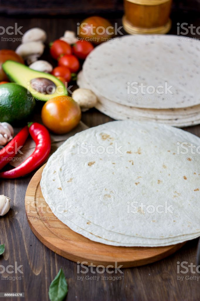 Homemade mexican tortillas with vegetables on table. stock photo