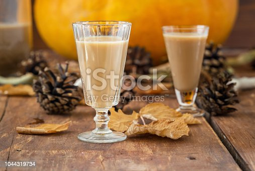 Homemade milk liqueur in glass from pumpkin, autumn drink holiday. Dry leaves
