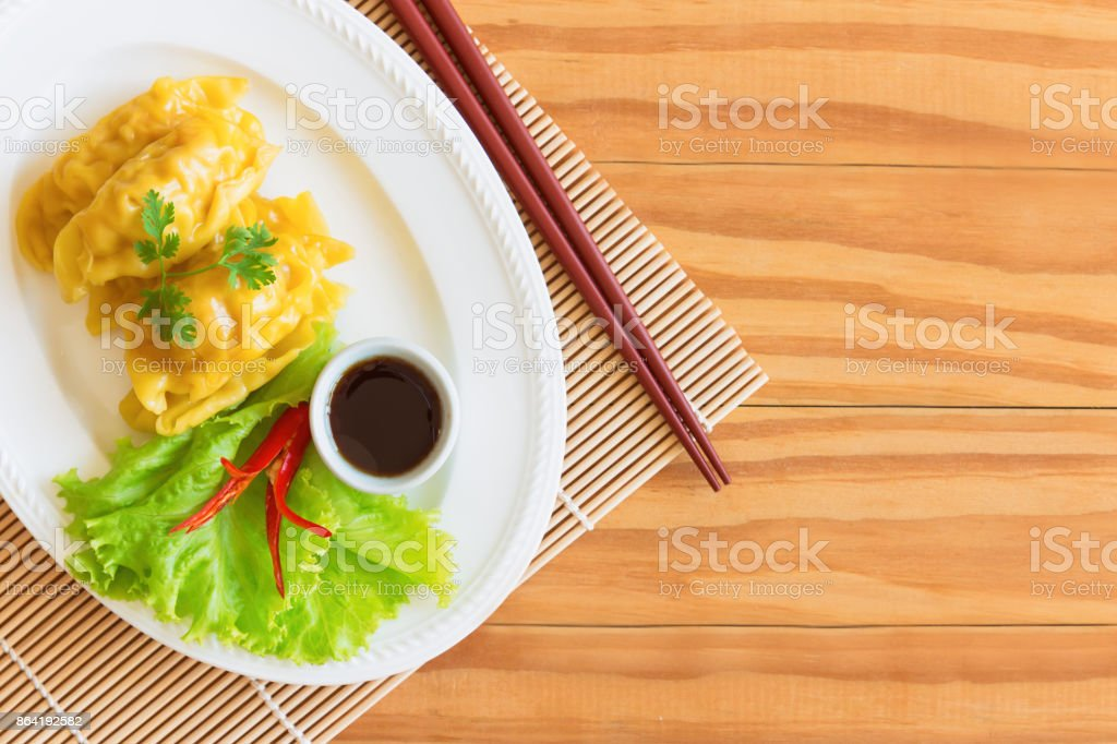 Homemade minced pork or shrimp dumpling and dipping soy sauce on wood table in top view flat lay with copy space. Delicious dumpling or dim sum for breakfast or dinner. Dim sum is Chinese food. royalty-free stock photo