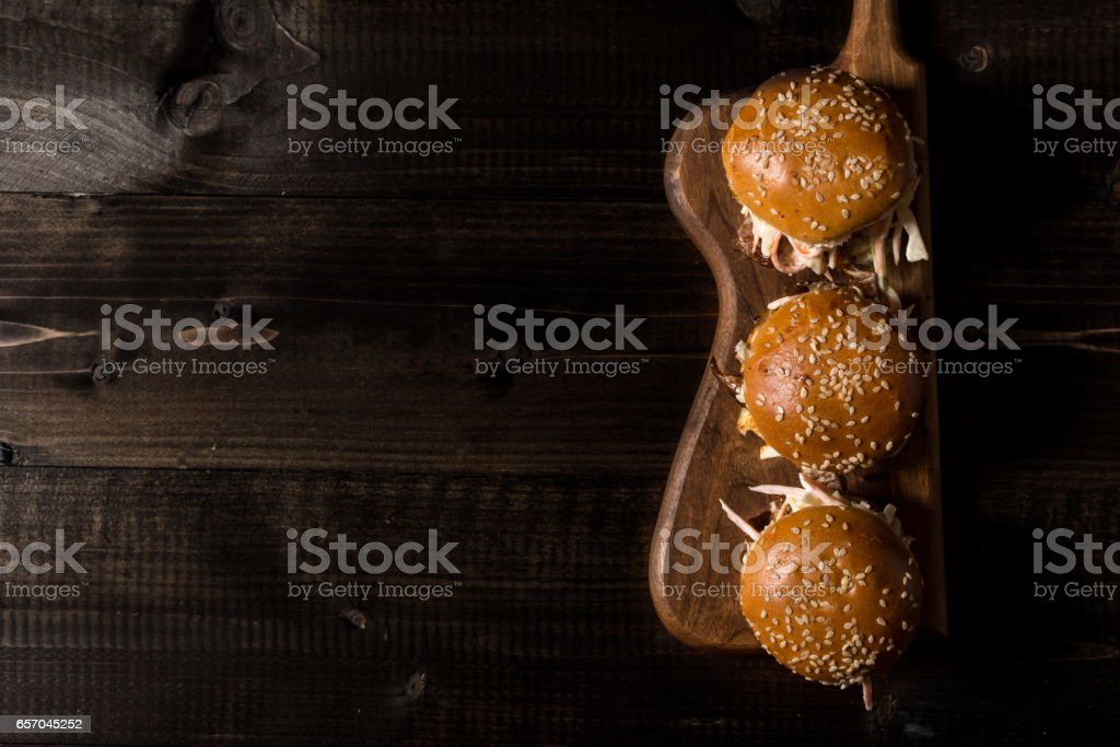 Homemade Mini Beef Burgers with Coleslaw Salad on Little Wooden Cutting Board. Barbecue Meat Sandwiches on Rustic Table. stock photo