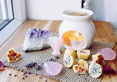 istock Homemade mini wax melts in aromatherapy lamp diffuser at home interior with rose quartz crystal hearts and angel for decoration on wooden window sill on winter. Seasonal spiritual zen concept. 1291462464