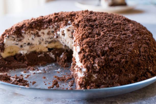 hausgemachte nerz mole hole kuchen mit schokolade biskuit, banane und frischkäse. - löcherkuchen stock-fotos und bilder
