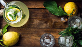 Homemade lemonade with mint and ice, served with fresh lemons over wooden background, top view, copy space. Food frame