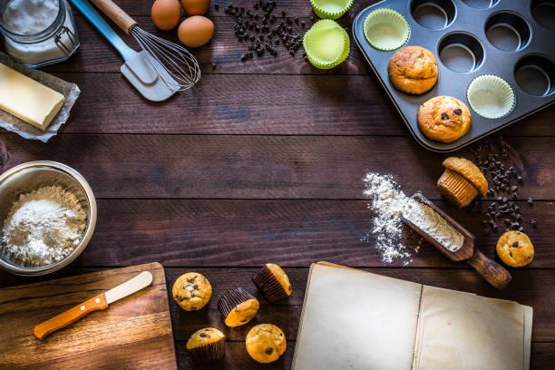 hausgemachte muffins und zutaten, um auf rustikalem holztisch mit kopierraum zu kochen - backrahmen stock-fotos und bilder