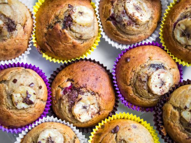 homemade muffins in bright paper with banana. top view - heiße schokoladen cupcakes stock-fotos und bilder