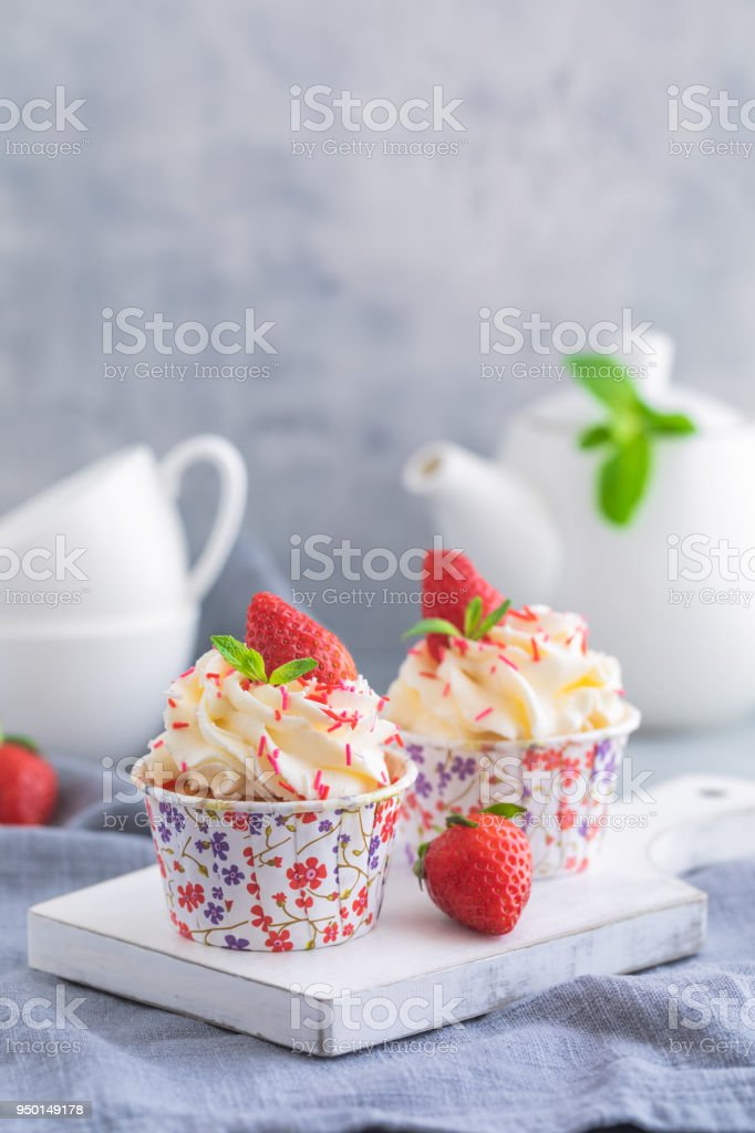 Homemade muffins or cupcakes with vanilla cream and fresh strawberries on the light grey background stock photo