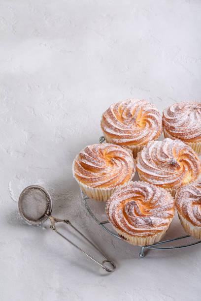 hausgemachte muffins mit puderzucker bestreuen. - vanille muffins stock-fotos und bilder