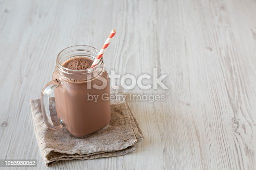 Homemade New England Chocolate Milkshake in a Glass Jar Mug on a white wooden background, low angle view. Copy space.